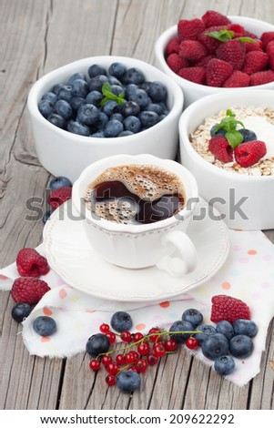 Delicious breakfast with coffee, oat flake and fresh berries on old wooden background - stock photo