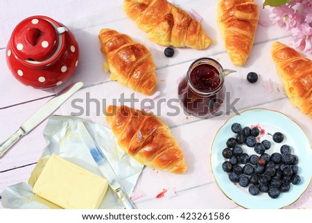 Delicious breakfast with fresh croissants and ripe berries on old wooden background,  - stock photo