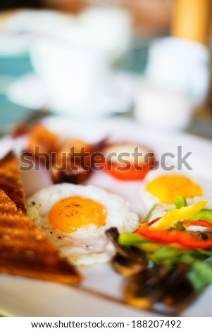 Delicious breakfast with fried eggs, vegetables and toast - stock photo