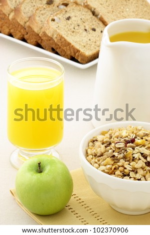 delicious breakfast with orange juice, green apple, whole grain bread and a healthy bowl of muesli cereal. - stock photo