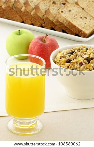 delicious breakfast with orange juice, whole grain bread,fresh apples and a healthy bowl of cereal. - stock photo