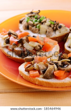 Delicious bruschetta with mushrooms on plate on table close-up