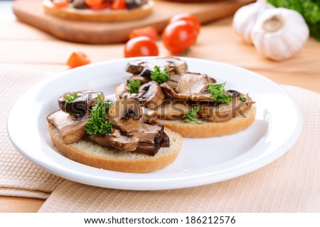 Delicious bruschetta with mushrooms on plate on table close-up - stock photo