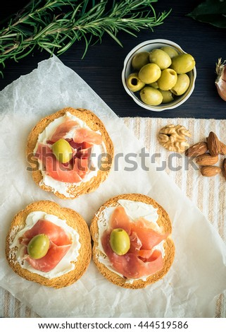 Delicious bruschetta with prosciutto and olives on background of rosemary, garlic, Bay leaf and nuts. Italian appetizer. Top view. Vertical. - stock photo