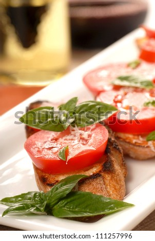 Delicious Bruschetta with tomato and basil on a white place with a glass of wine in the background along with an oil and vinegar vinaigrette. - stock photo