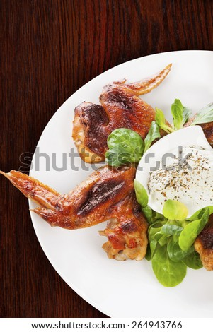 Delicious buffalo wings with fresh salad on brown wooden background. Culinary eating.  - stock photo