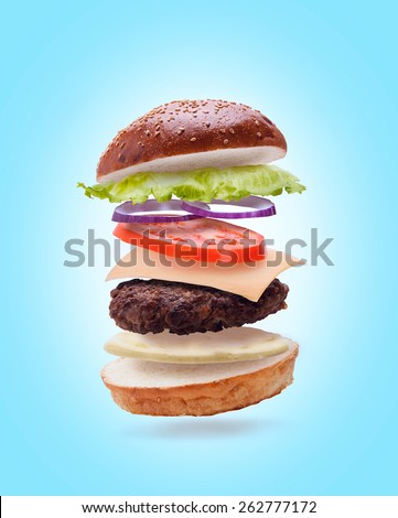 delicious burger with flying ingredients on light blue background