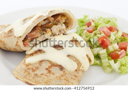 Delicious burrito brunch of sausage cut in half on white plate - stock photo