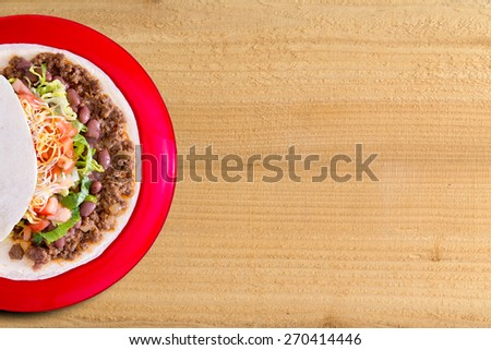 Delicious burrito filled with spicy ground beef , beans and salad topped with cheese on a colorful red plate, overhead view on a wood background with copy space - stock photo
