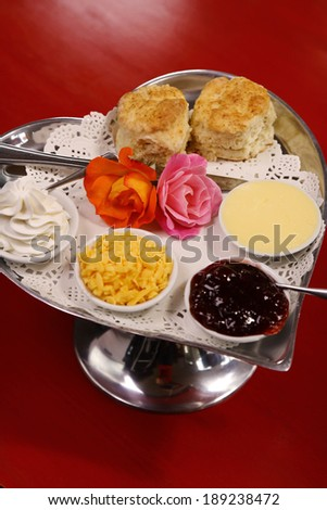 Delicious butter scones on a silver heart shaped tray served with roses cheese cream and jam preserves on a red wooden table. - stock photo