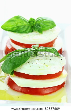 Delicious Caprese Salad made with mozzarella cheese, fresh basil, and tomatoes. - stock photo
