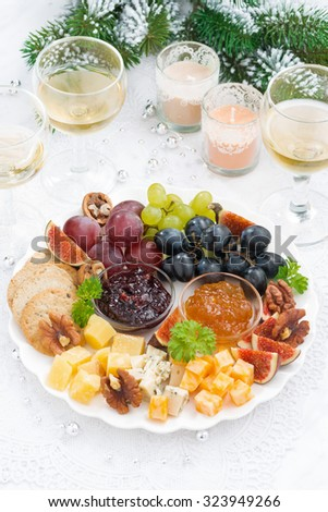 delicious cheese and fruit plate to the holiday on table, top view, vertical - stock photo