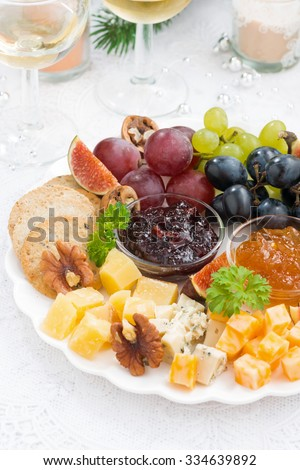 delicious cheese and fruit plate to the holiday on table, vertical - stock photo
