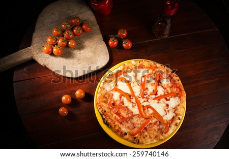 Delicious cheese and pepper pizza with red tomatoes on wooden table - stock photo