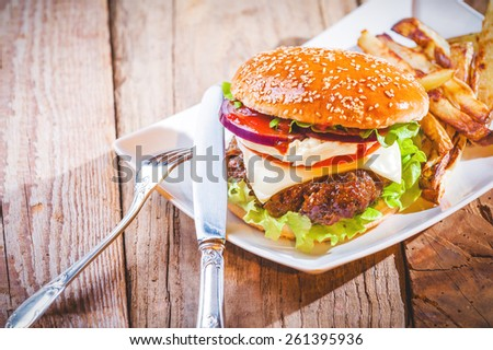 Delicious cheeseburger and french fries on a white plate on a wooden rustic table. - stock photo