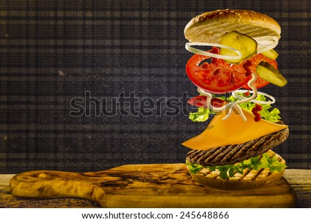 Delicious cheeseburger stacked high with a juicy beef patty, cheese, fresh lettuce, onion and tomato with flying ingredients and copyspace - stock photo