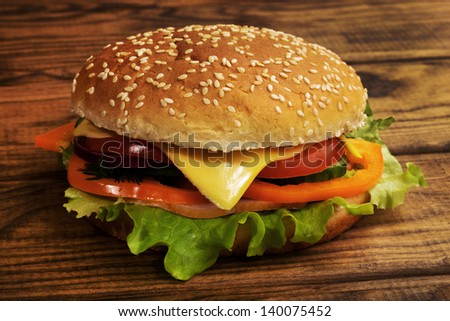 Delicious cheeseburger stacked high with a juicy ham , cheese, fresh lettuce, onion and tomato on a fresh bun with  standing on  wooden table  - stock photo