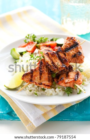 Delicious chicken masala skewers with rice and vegetable salad. - stock photo