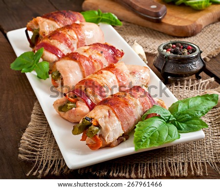 Delicious chicken rolls stuffed with green beans and carrots wrapped in strips of bacon - stock photo