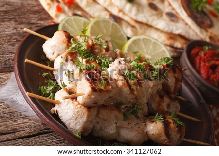 Delicious chicken tikka kebabs on skewers close-up on a plate. horizontal