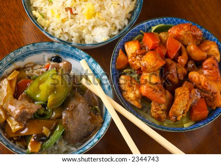 Delicious Chinese meal, with stir-fried beef in black bean sauce, chicken with cashew carrot in yellow bean sauce, rice, with chopsticks