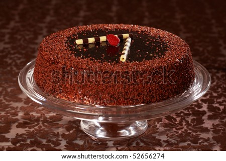 Delicious chocolate cake garnished with fruits and small chocolate rolls - stock photo