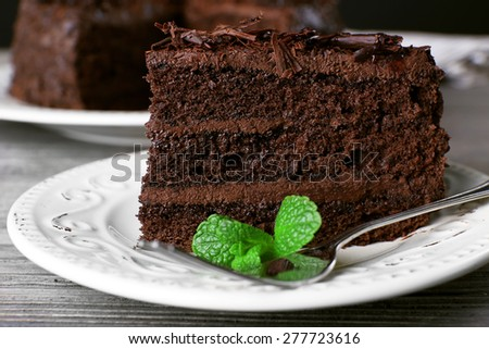 Delicious chocolate cake in white plate with mint on wooden table background, closeup - stock photo