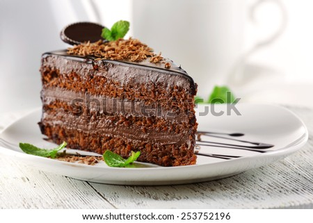 Delicious chocolate cake on plate on table on light background - stock photo