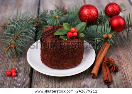Delicious chocolate cake on saucer with holly and berry on Christmas decoration and wooden background - stock photo