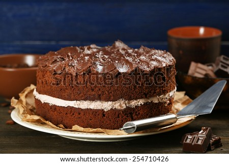 Delicious chocolate cake on table on blue background - stock photo