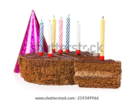 Delicious chocolate cake with candles, gift box and birthday cap, isolated on white background - stock photo