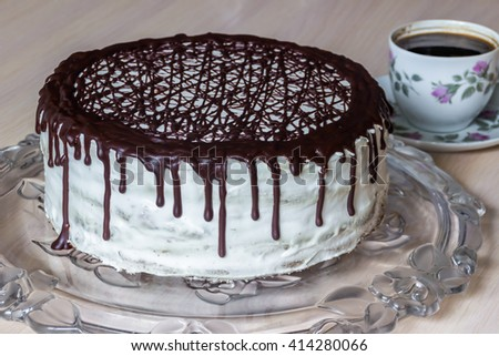 Delicious chocolate cake with creamy cream and cup of coffee on the table - stock photo