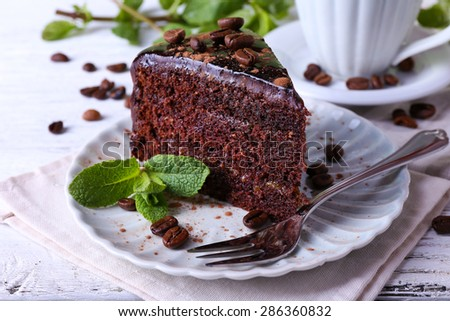 Delicious chocolate cake with mint on plate on table close up