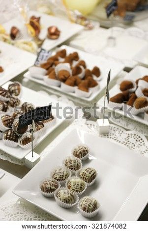 Delicious chocolate candies on plates on table close up - stock photo