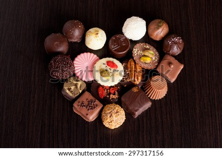 Delicious chocolate candies on wooden background, horizontal - stock photo