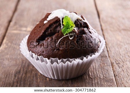 Delicious chocolate cupcake on wooden table close up