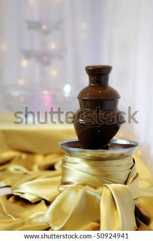 Delicious chocolate fondue fountain on a table - stock photo