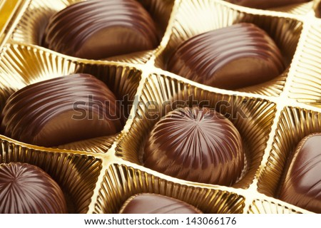 Delicious chocolate pralines in the golden box - stock photo