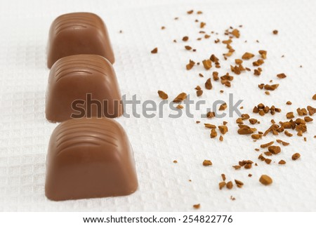 Delicious chocolate pralines on white towel - stock photo