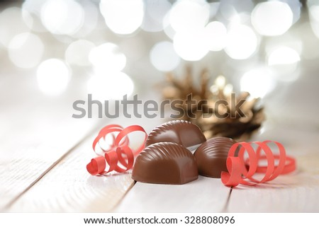 Delicious chocolate pralines on wooden table with blurred lights - stock photo