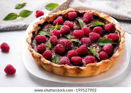 Delicious chocolate tart with raspberry on the white plate - stock photo