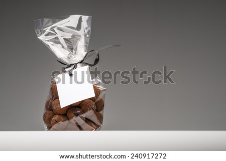 Delicious chocolate truffles bag isolated on grey background. Right copy space. Blank label that you can add your own trademark or your own message. Fun composition and lighting. Shooting in studio. - stock photo