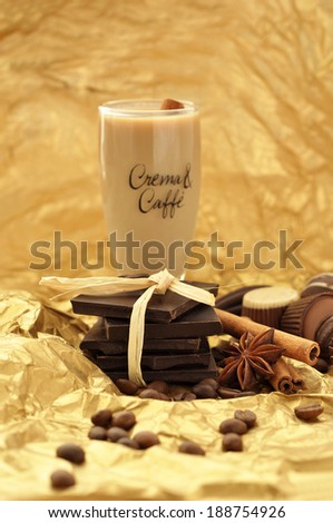 Delicious chocolates and spices on a golden background - stock photo