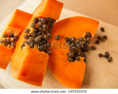 Delicious chopped ripe papaya fruit on the cutting board - stock photo