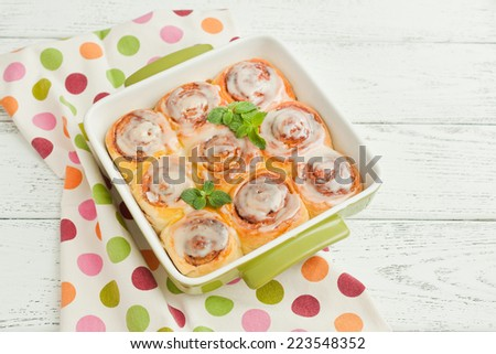 delicious cinnamon rolls coated with white chocolate glaze on wooden background. - stock photo