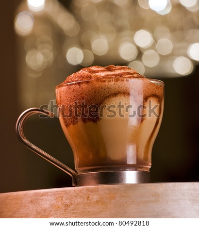 Delicious coffee drink called caffe macchiato, which is espresso with milk and foam and added chocolate syrup for layered effect. Served on a bar in a glass cup. Sparkling lights   in the background. - stock photo