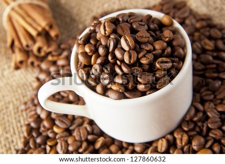 Delicious Coffee in a White Ceramic Cup on a Saucer, Roasted Coffee Beans, Cinnamon on a Sacking background - stock photo