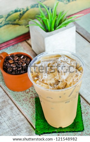 Delicious cold coffee drink with ice on wooden table.Shallow depth of field. - stock photo