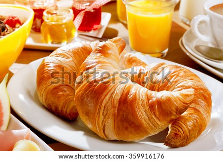 Delicious continental breakfast with fresh flaky croissants, assorted preserves, orange juice , cereal and coffee, close up on the croissants - stock photo