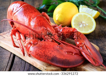 Delicious cooked lobster on wooden cutting board with fresh lemons and parsley at the  background - stock photo